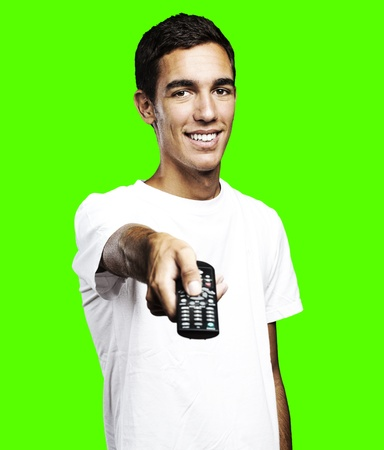 pointing device: portrait of young man pointing with remote control against a removable chroma key background
