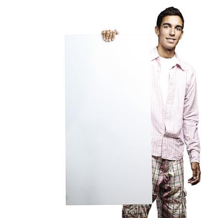 Retrato de hombre joven y sonriente y sosteniendo un cartel en el fondo blanco
