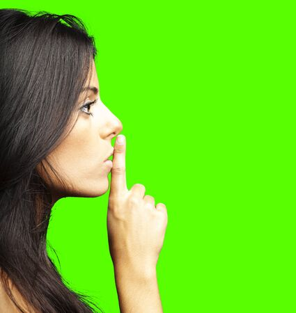 portrait of young woman doing silence sign against a removable chroma key background photo