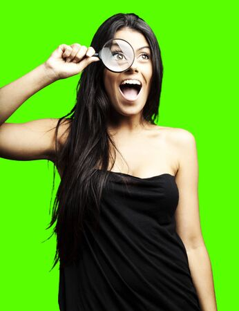 portrait of young woman looking through a magnifying glass against a removable chroma key background photo