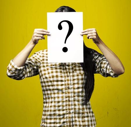 signo de interrogacion: Retrato de mujer llegando detrás del símbolo de interrogación sobre fondo azul Foto de archivo