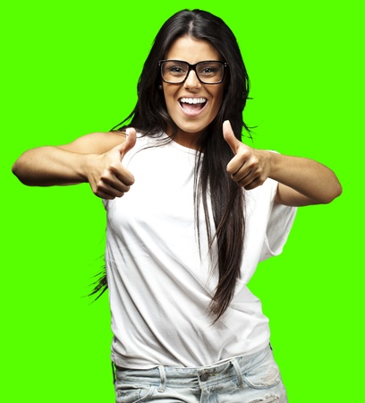 portrait of young woman doing good symbol against a removable chroma key background photo