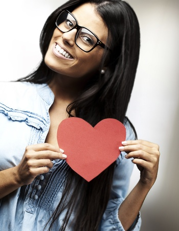 doctor holding gift: portrait of pretty woman holding a heart against a abstract background Stock Photo