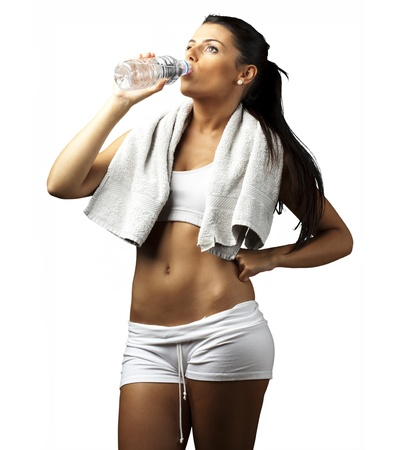 portrait of young woman wearing sport clothes and drinking water against a white background photo