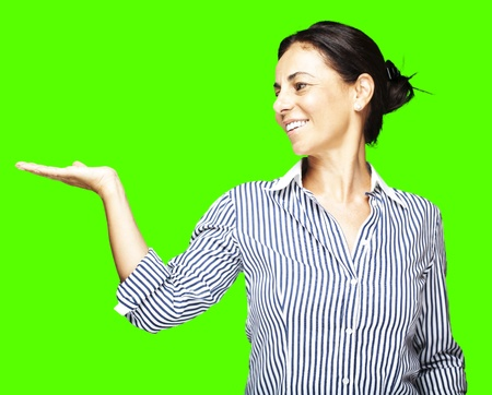 portrait of a middle aged woman holding gesture against a removable chroma key background photo