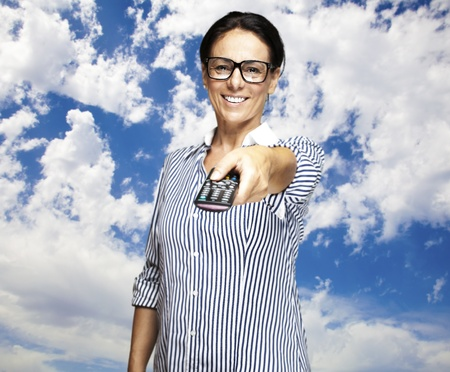 portrat of a middle aged woman using tv control against a cloudy sky photo