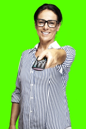 portrait of a middle aged woman changing channel against a removable chroma key background photo