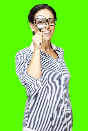 portrait of a middle aged woman looking through a magnifying glass against a removable chroma key background photo