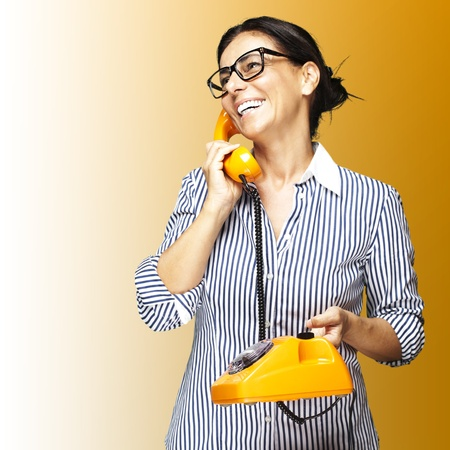 portrait of middle aged woman wearing glasses with vintage telephone on yellow background Stock Photo - 11507244