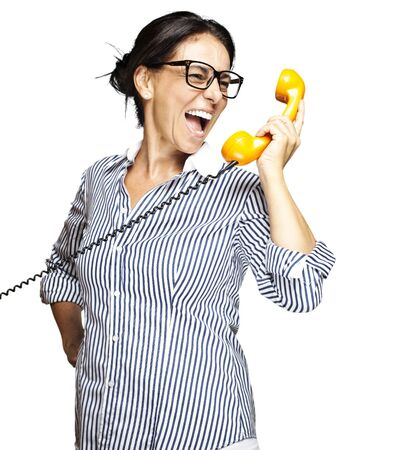 portrait of a middle aged woman talking on vintage telephone over white photo