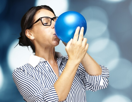 portrait of a middle aged woman blowing a balloon against a abstract background photo