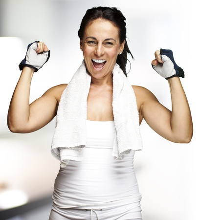 exercise room: portrait of a middle aged woman gesturing win symbol indoor