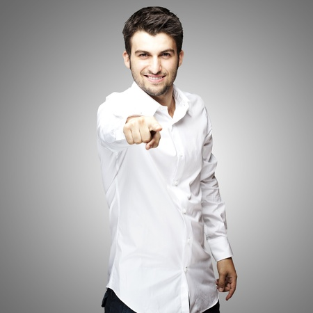 portrait of young man pointing with finger against a grey background photo