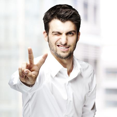 clin d oeil: portrait d'un beau jeune homme gestes bon symbole sur fond abstrait Banque d'images