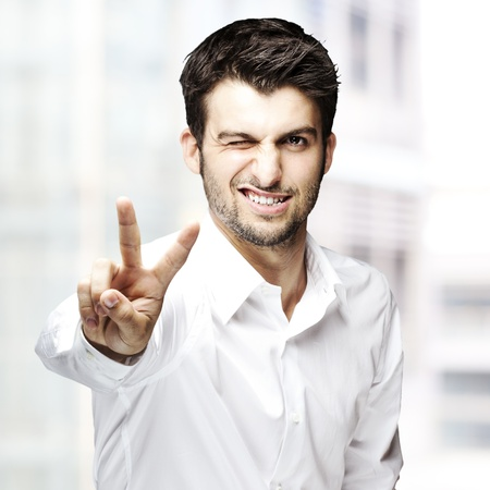 portrait of a handsome young man gesturing good symbol against abstract background photo