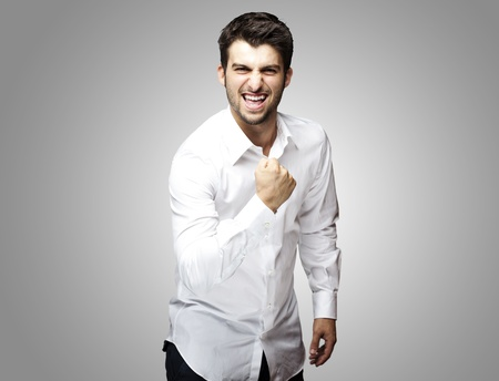 portrait of young man winner gesture against a grey background Stock Photo - 11507173