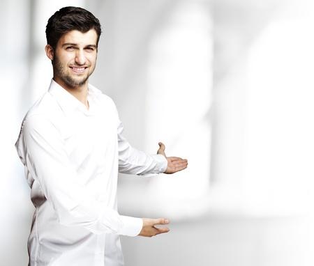 invitando: retrato de un apuesto joven haciendo un gesto de bienvenida en interiores