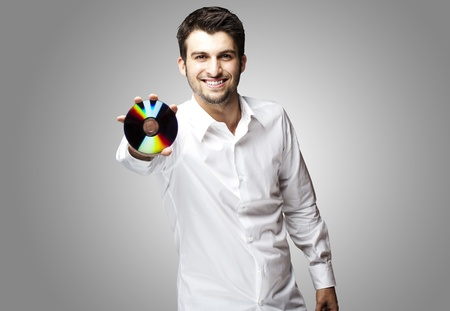 portrait of a handsome young man holding cd against a grey background photo