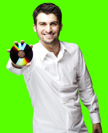 portrait of young man holding cd against a removable chroma key background photo