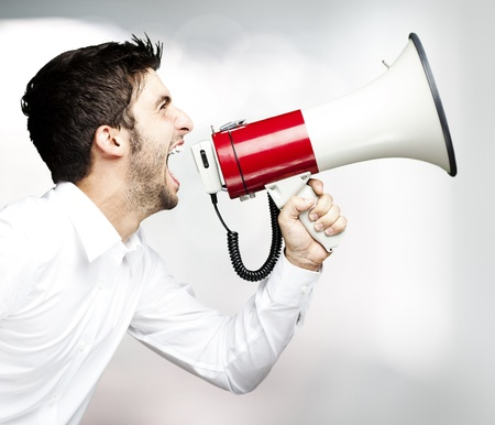 portrait of young man handsome shouting using megaphone indoor photo