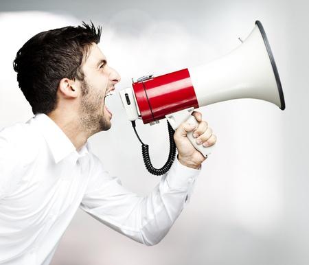 hombre megafono: Retrato de hombre joven y guapo gritando con el meg�fono en interiores Foto de archivo