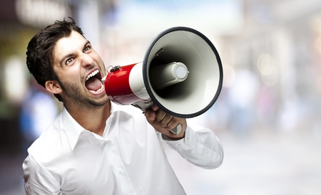 portrait of young man shouting with megaphone at crowded place Stock Photo - 11507122