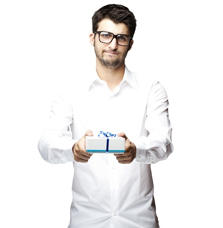 portrait of a handsome young man showing a gift over a white background photo