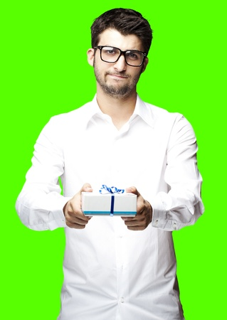 portrait of young man giving a gift against a removable chroma key background photo