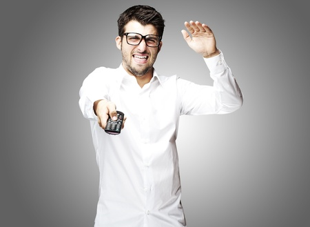 portrait of angry young man using tv control over grey background photo