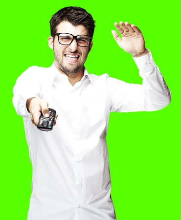 portrait of angry man changing channel using a remote tv control over removable chroma key background Stock Photo - 11507115