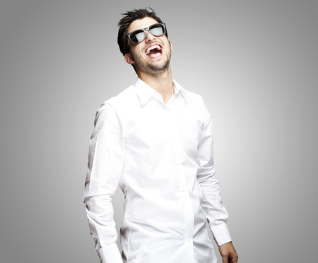 shades of grey: portrait of a handsome young man with sunglasses enjoying over grey background