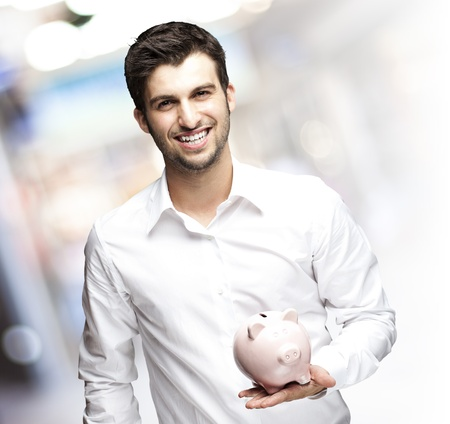portrait of young man holding a piggy bank against a crowded place photo