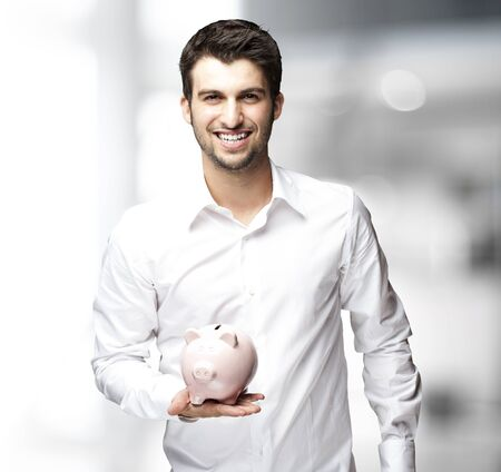 Portrait of young man holding a piggy bank indoor photo