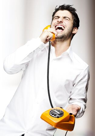 portrait of young man handsome laughing using a vintage telephone indoor Stock Photo - 11506851