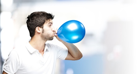 portrait of young man blowing a balloon indoor photo