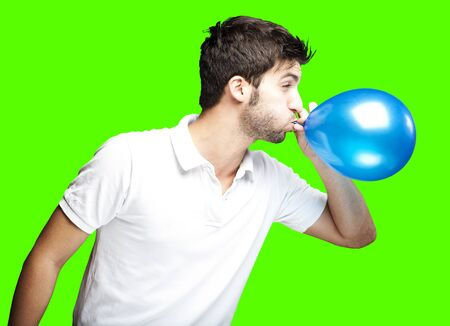 portrait of young man blowing a balloon over removable chroma key background photo