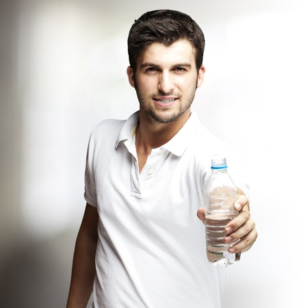 offerings: portrait of a handsome young man offering a water bottle indoor Stock Photo