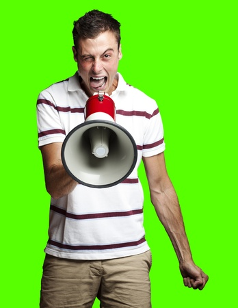portrait of young man shouting with megaphone against a removable chroma key background photo