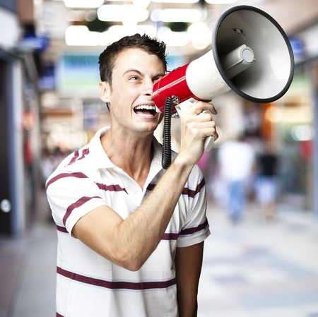 portrait of young man shouting with megaphone at crowded place photo
