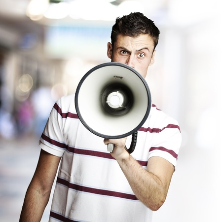 portrait of young man shouting using megaphone against a crowded place photo