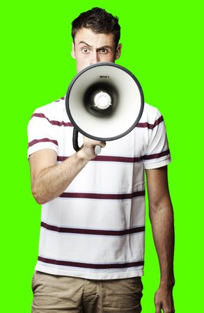 portrait of young man shouting with megaphone over removable chroma key background photo