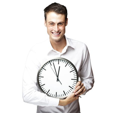 against the clock: portrait of young man holding clock against a white background Stock Photo