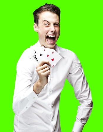 portrait of a lucky young man showing poker cards over a removable chroma key background photo
