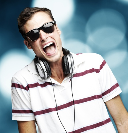 portrait of a handsome young man listening music with headphones against a abstract background photo
