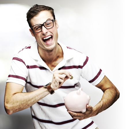 portrait of young man saving coins in piggy bank indoor photo