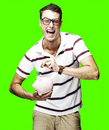 portrait of a crazy young man holding a piggy bank over a removable chroma key background photo