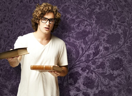 portrait of young student holding books against a vintage wall photo
