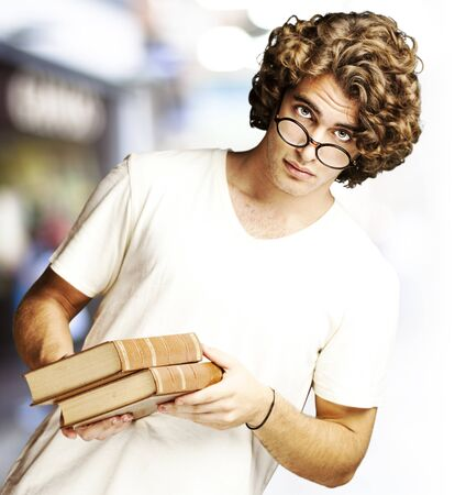 portrait of young student holding books against a library photo