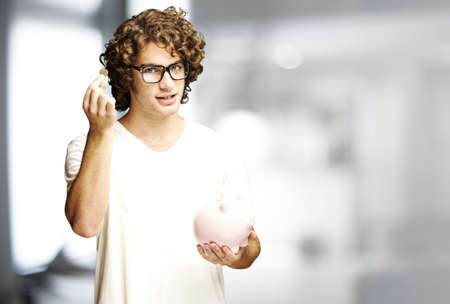 portrait of young man holding coin and piggy bank indoor photo