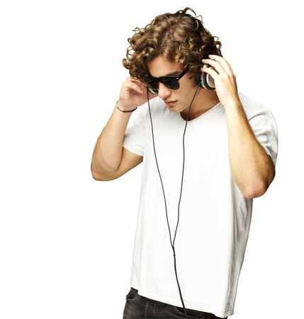 music listening: portrait of a handsome young man listening music against a white background